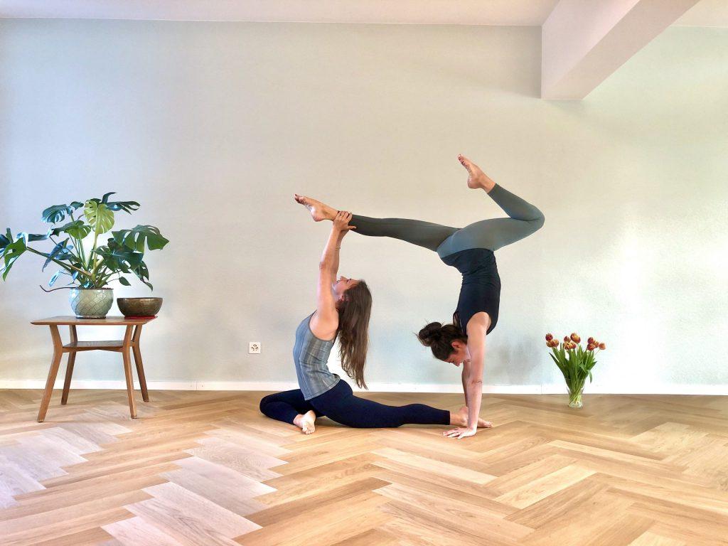 Kim ist in der Taube, Anna im Handstand für die Yogalehrer-Ausbildung